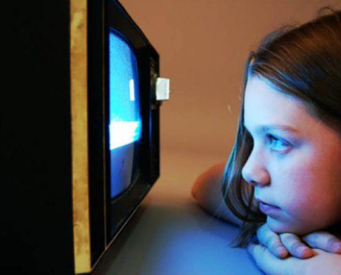 young girl watching a screen