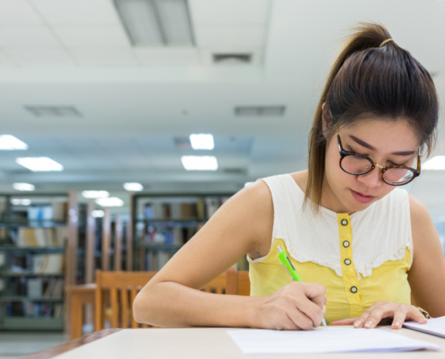 high school student writing an sat essay in the library