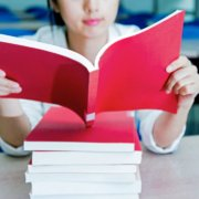 young woman reading a red book on a stack of other red books